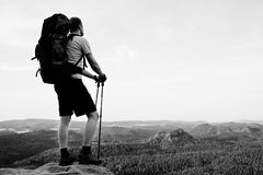 Tall backpacker with poles in hand. Sunny summer evenng in rocky mountains. Hiker with big backpack stand on rocky view point abov Stock Photo