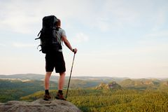 Tall backpacker with poles in hand. Sunny summer evenng in rocky mountains. Hiker with big backpack stand on rocky view point abov Royalty Free Stock Photos