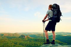 Tall backpacker with poles in hand. Sunny summer evenng in rocky mountains. Hiker with big backpack stand on rocky view point abov Stock Images