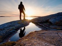 Tall backpacker watch clear sunny daybreak over sea. Hiker  Hiker enjoy breathtaking sunrise Royalty Free Stock Images