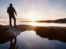 Tall backpacker watch clear sunny daybreak over sea. Hiker  Hiker enjoy breathtaking sunrise Stock Images