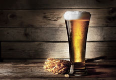 Tall beer glass with beer and ears. On wooden background stock photo