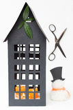 Tall Black Paper House with Leaves, Candles and a Snowman Stock Images