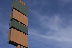 Tall blank signboard with alternating panels. In green and brown with copyspace for your text ot information against a hazy blue sky Royalty Free Stock Photography