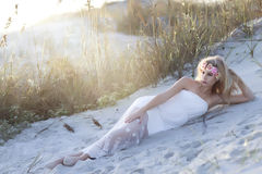 A tall blond woman laying in the sand with floral wreath on her head. Stock Photo