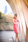 Tall blond woman standing in coral halter dress in front of The Pavillion near Lincoln Park Zoo in Chicago, Illinois. Young, tall blond woman with coral halter Stock Photo