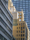 Tall brick and glass buildings at busy and crowded Manhattan  Royalty Free Stock Images