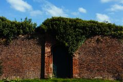 Tall brick wall with closed garden gate Royalty Free Stock Photography