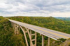 Tall bridge crossing a tropical valley Stock Photo