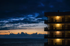 The tall building against the cloudscape and the sea. Silhouette of a woman stands on the balcony of a tall hotel building and admire the sunset over the sea Stock Photos