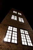 Tall building with brick walls and big windows Stock Photo