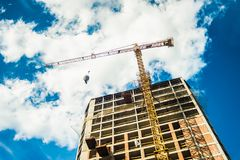 Tall building construction and crane under a blue Stock Photography