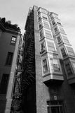 Tall building with fire escape and bay windows. Black and white image of an old tall apartment building in downtown boston showing two rows of bay windows and Royalty Free Stock Image