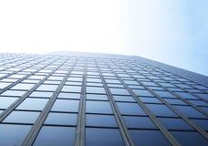 Tall Building Office Windows. Glass office windows on an upward tall building against hazy sunny sky. Room for text stock photos