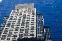 Tall building reflect on clear blue glass window of tall building. A Tall building reflect on clear blue glass window of tall building stock photo