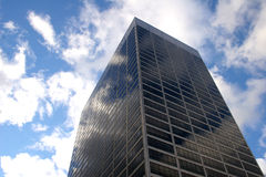 Tall Building with Reflecting Clouds. A tall building with clouds and blue sky reflecting on its windows royalty free stock photos