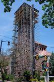 Tall Building Tower Repair With Scaffolding. Tall stone church building tower exterior under repair construction with tall scaffolding, steps and ladder and stock images