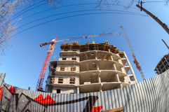 Tall building under construction with crane Stock Photo