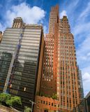 Tall buildings against a blue sky with white clouds royalty free stock photos
