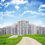 Tall buildings, green hills and road against sky Royalty Free Stock Photos