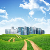 Tall buildings, green hills and road against sky Stock Photos