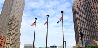 Tall buildings and three flags. Impressive tall buildings and three colorful flags waving in the breeze on a early morning in the city Royalty Free Stock Photos