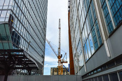 The tall business skyscrapers and the construction crane i Royalty Free Stock Image