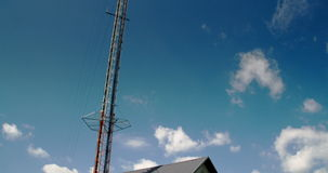 Tall cellular tower beside a small house 4K FS700 Odyssey 7Q Stock Photography