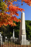 Tall Cemetary Stone. White cemetery stones under an orange maple tree Royalty Free Stock Photos