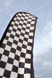 Tall checkered flag waving in the wind against the sky stock images