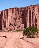 Tall Cliffs. Tire tracks in the sand leading to red cliffs. Taken in the desert in Argentina royalty free stock photography