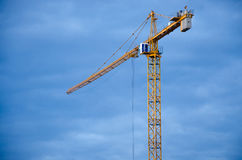 Tall construction crane against blue clear sky. Building at the construction site Royalty Free Stock Photos