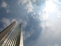 Tall Corporate Tower Below Clouds. A tall corporate structure below clouds and sun royalty free stock images
