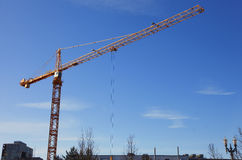 Tall crane at work. Stock Photo