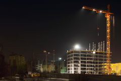Tall cranes and brick buildings under construction Royalty Free Stock Images