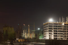 Tall cranes and buildings under construction Stock Images