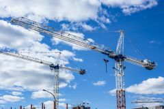 Tall cranes on construction site clouds blue sky Stock Photo