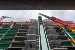 Tall cranes and construction workers Stock Images