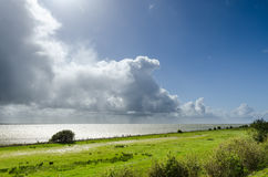 Tall cumulus clouds along the coast of lake IJsselmeer. Tall cumulus and rain clouds along the coast, IJsselmeer, The Netherlands Stock Photo