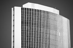 Tall curved office building in black & white. Monochrome of tall, modern office building Royalty Free Stock Photography