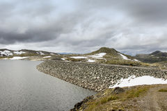 Tall dam in Norway made of huge heap of stones Royalty Free Stock Image