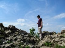 A tall dark-haired young man stands on a rock and looks down - view from the back. Clear sunny day, stone boulders and one adult. Guy against the sky stock image