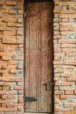 Tall door on the brick wall. There is a tall wooden door on the wall which made by blocks of brick stock photography