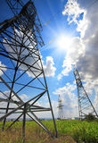 Tall electric masts against sun and sky Royalty Free Stock Images