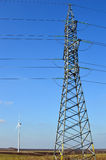 Tall electric tower, wind generator seen far in the distance Royalty Free Stock Images
