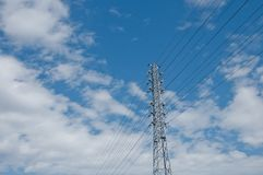 Tall electricity power line grid generator pole with blue sky. And clouds above. The power line provides electricity to the whole city Stock Photo