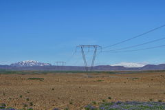 Tall electricity pylons leading high electric current with a high mountains and blue sky in the background in Iceland Royalty Free Stock Images