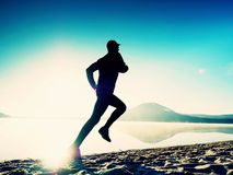 Tall fit man running along the sea shore in morning. Healthy male jogging on beach. Tall fit man running along the sea shore in morning. Healthy male jogging on Royalty Free Stock Image