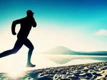 Tall fit man running along the sea shore in morning. Healthy male jogging on beach. Tall fit man running along the sea shore in morning. Healthy male jogging on Stock Images