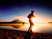 Tall fit man running along the sea shore in morning. Healthy male jogging on beach. Tall fit man running along the sea shore in morning. Healthy male jogging on Stock Photos